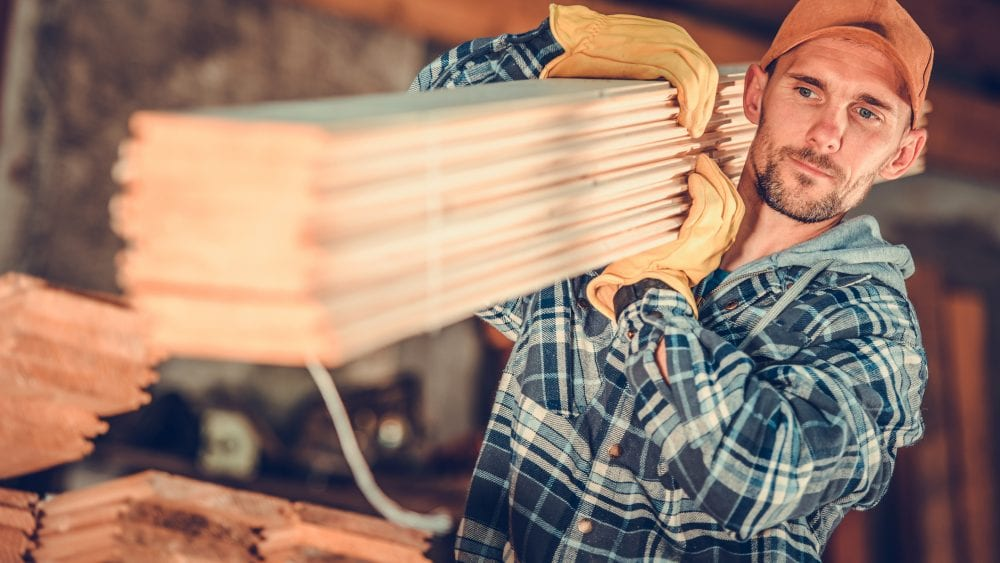 Construction worker shouldering planks of wood representing the need to transfer contractual risk.
