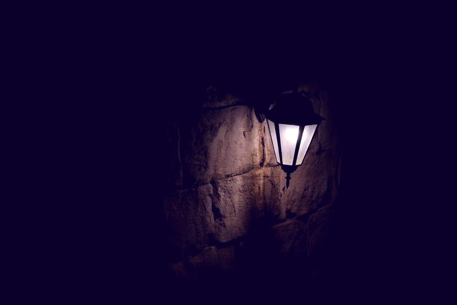A dark lamp on an exterior stone wall that is flickering and buzzing indicating a wiring issue.