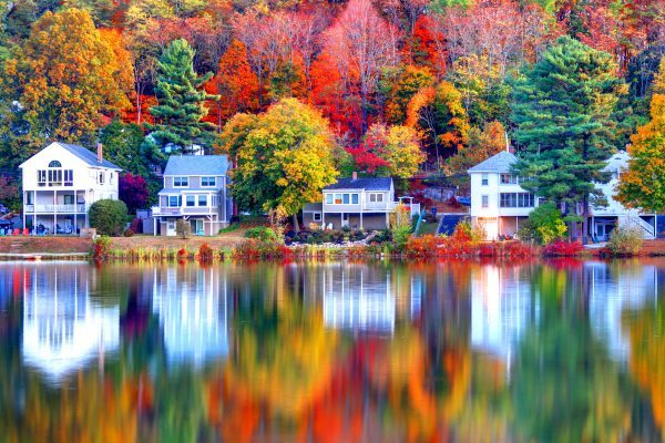 Lakeside home insurance houses surrounded with bright fall trees.