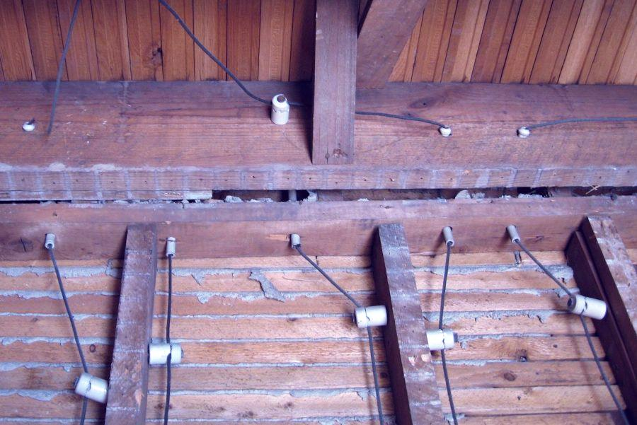 Interior wall behind plaster showing knob and tube electrical wiring.