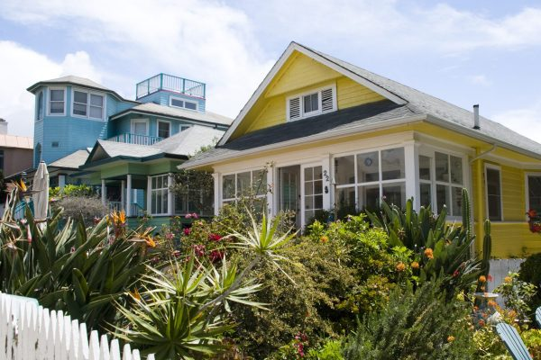 Row of colorful specialty home insurance beach houses with white picket fencing.