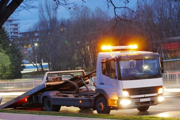A rollback tow truck on the side of a road at dusk. Insurance pays.