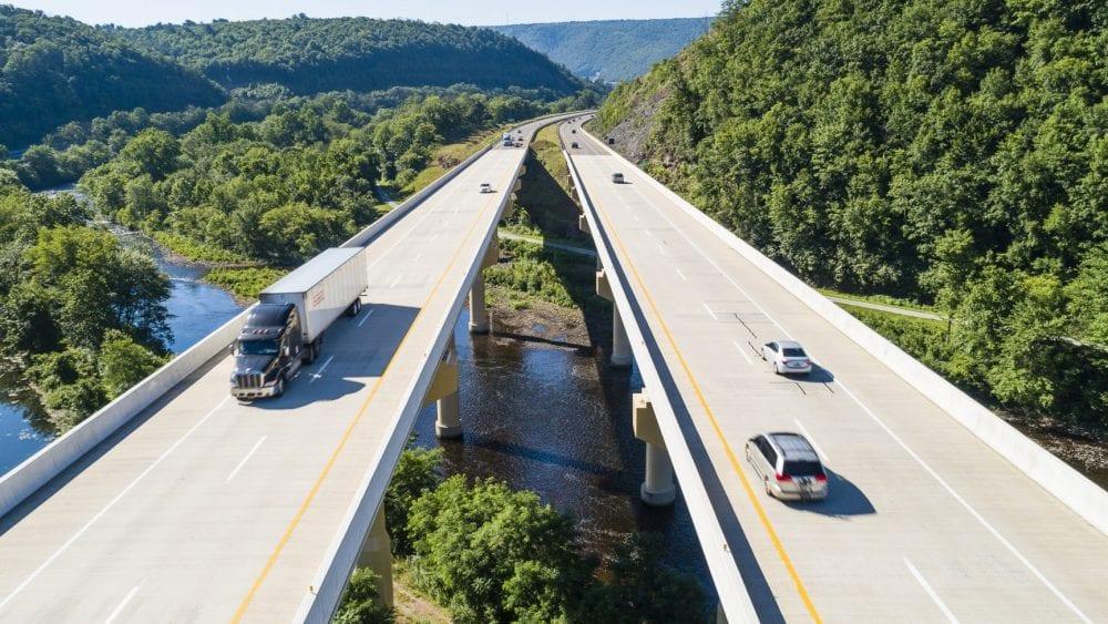 Private passenger vehicles and trucks on a bridge.