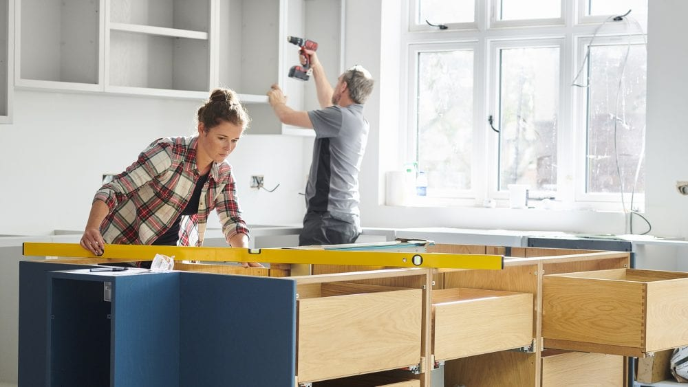 Construction workers fitting kitchen cabinets.
