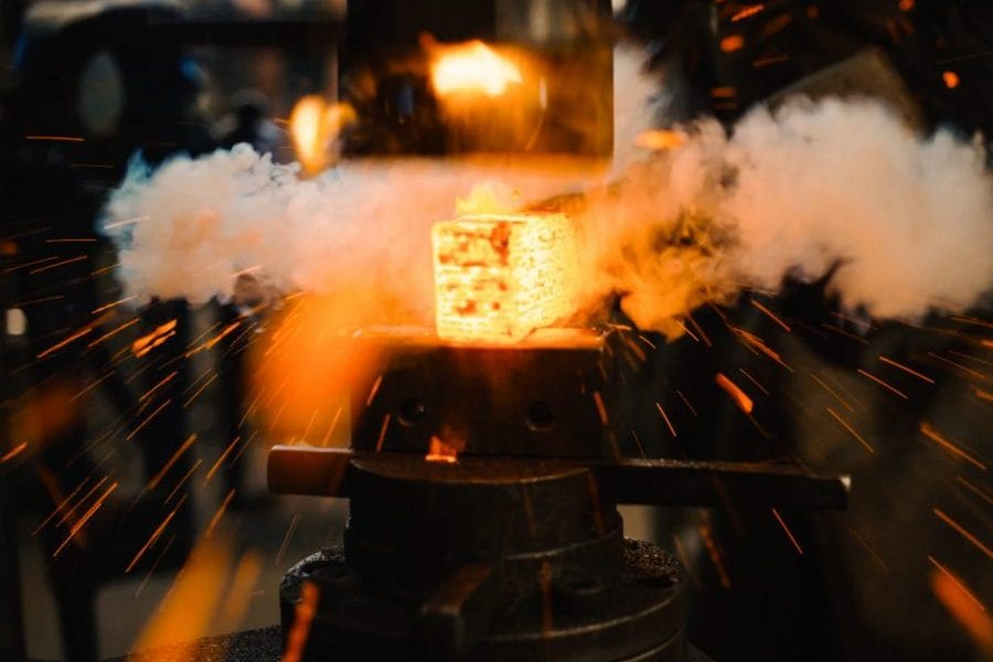Manufacturer hammer forges hot, glowing iron into desired shape.