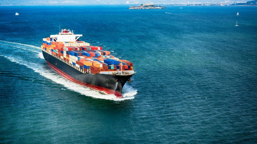 A cargo ship loaded with multi-colored containers protected by manufacturers insurance.