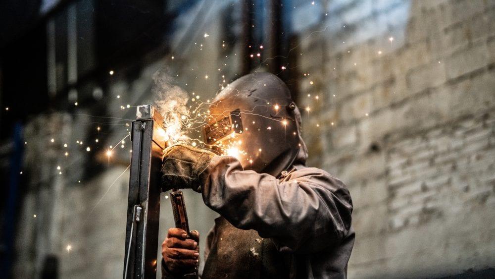 Factory worker welds steel.