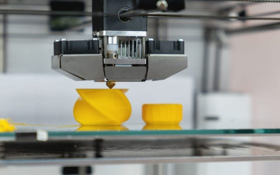 3D printer printing a yellow twisty model symbolizing claim analytics in manufacturers insurance