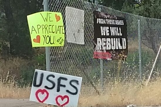 Paper signs on chain link fence announcing We Appreciate You, USFS, and From These Ashes We Will Rebuild.