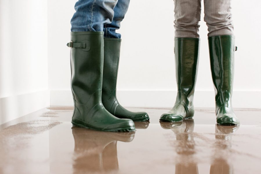 Two pair of green rubber boots on wet, flooded floor.