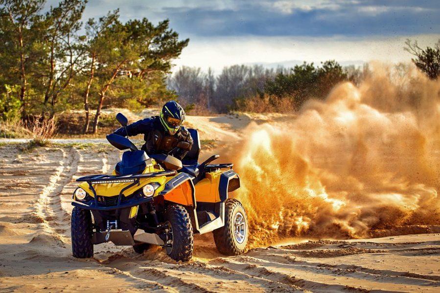 Blue and yellow ATV racing on sand.