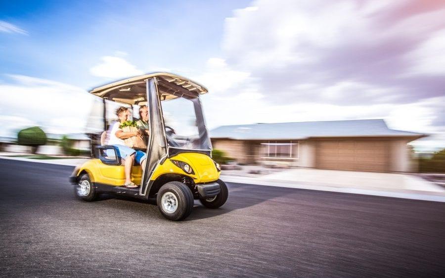 Golf cart on town street motion blur.