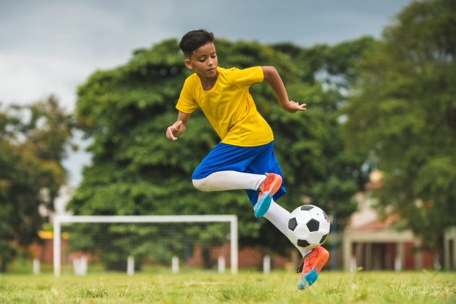 Young, healthy child playing soccer representing the perfect time to buy life insurance for kids.