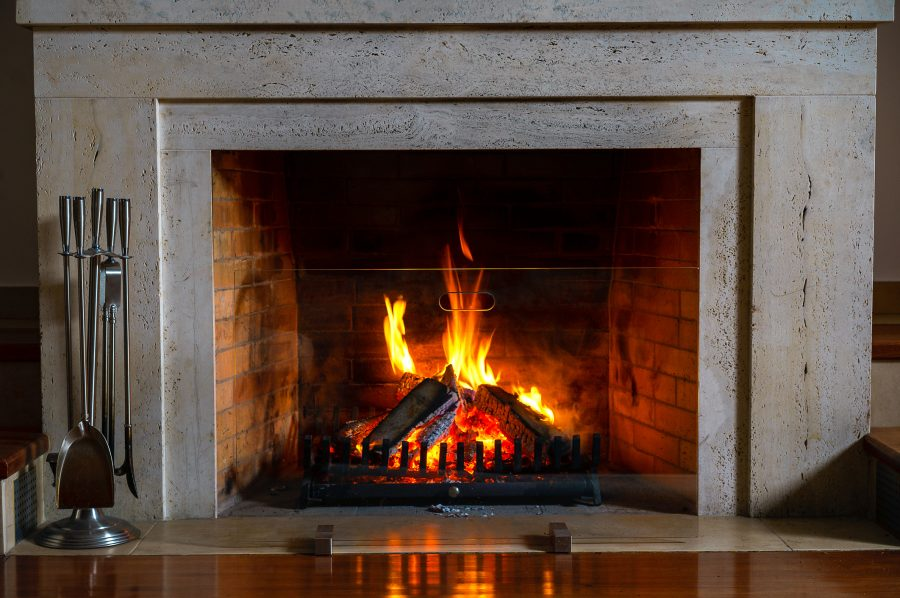 A fireplace with fire and clean and safe surrounding area.
