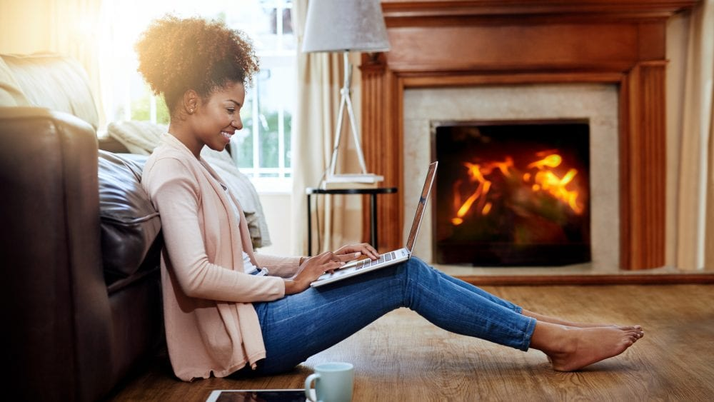 A homeowners insurance client in front of her fireplace.