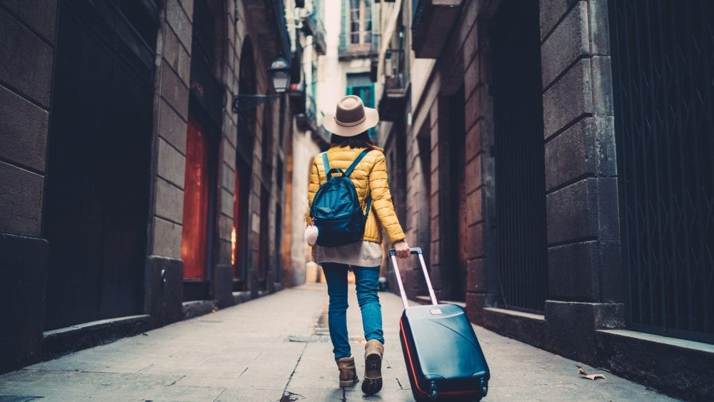 Young woman walking stone street with suitcase, secure with travel insurance .