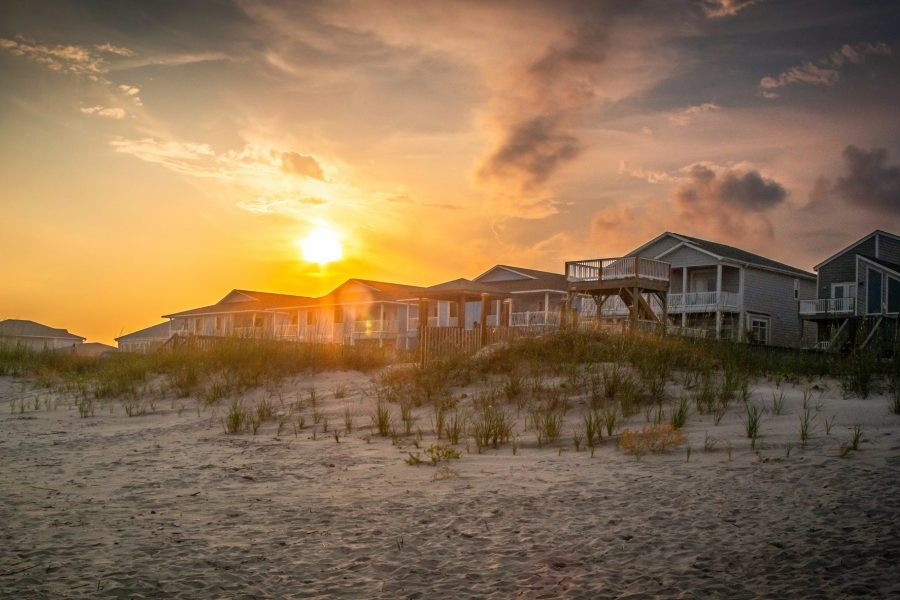 A brilliant sky hovers over vacation homes atop sand dunes.