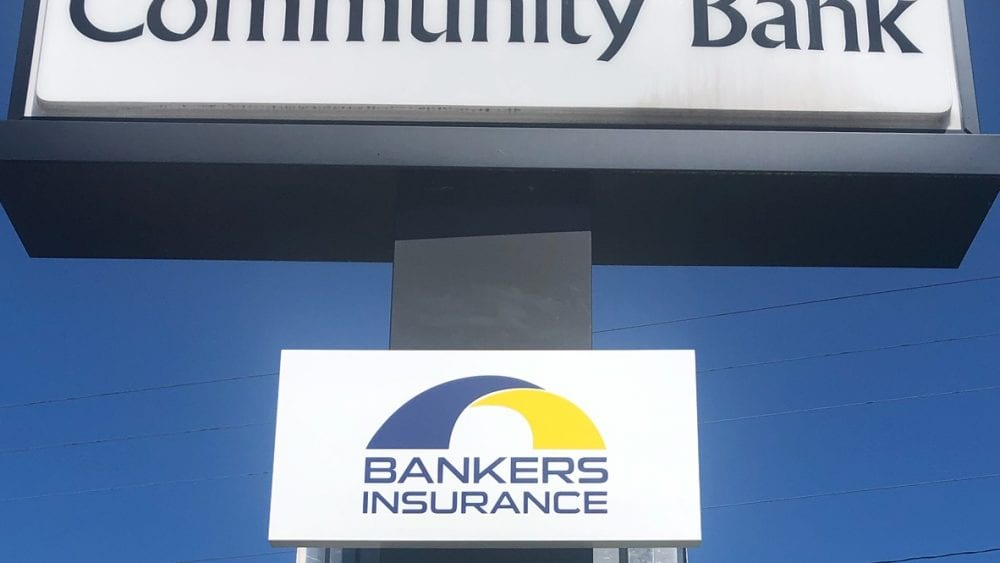 Bankers Insurance sign beneath First Community Bank sign.