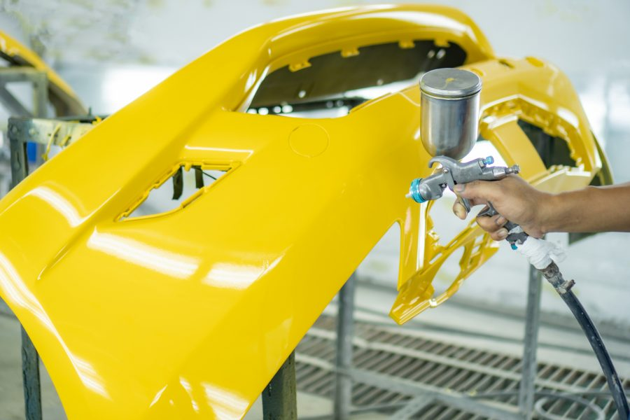 Aftermarket car bumper in a paint booth being sprayed bright yellow.