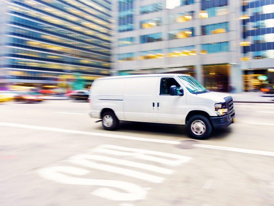 Commercial white van in city.