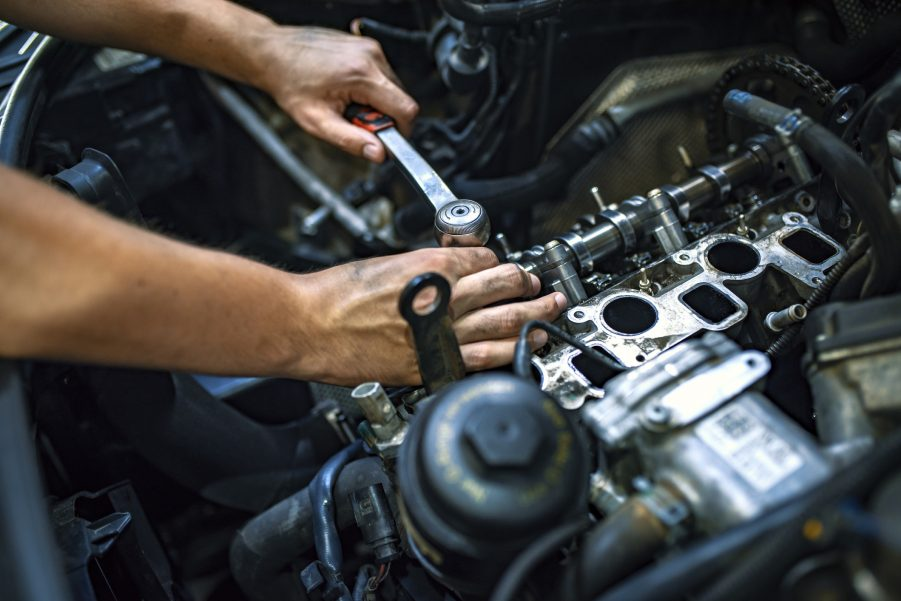 Car mechanic using OEM auto parts to fix an engine.