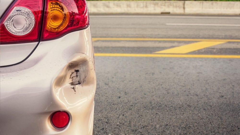 Dented rear corner of a car bumper in a parking lot.