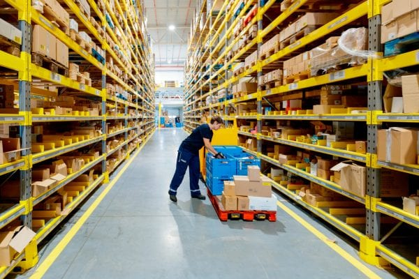 Female warehouse worker arranging items into crate.