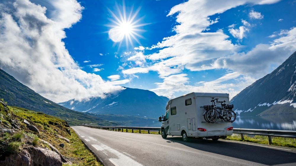 RV with bikes strapped on back on mountain road with blue sky and sunshine.
