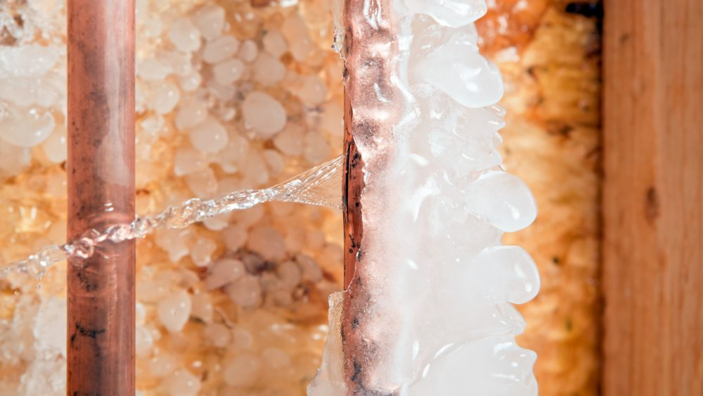 Frozen copper pipe with crack and spewing water into a home.