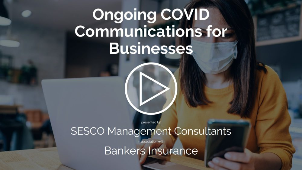 Masked business owner due to COVID with, laptop and phone.