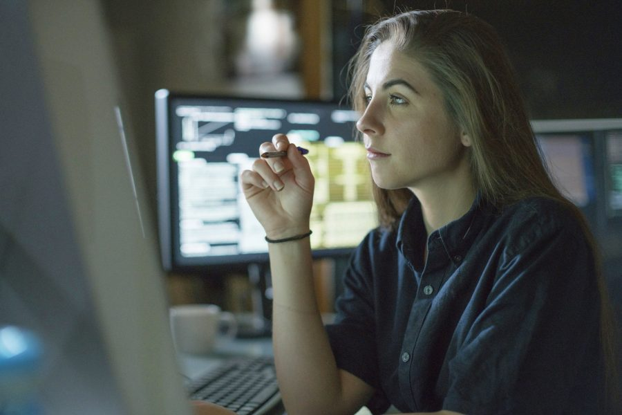A young woman seated at desk staring at computer and contemplating theft.