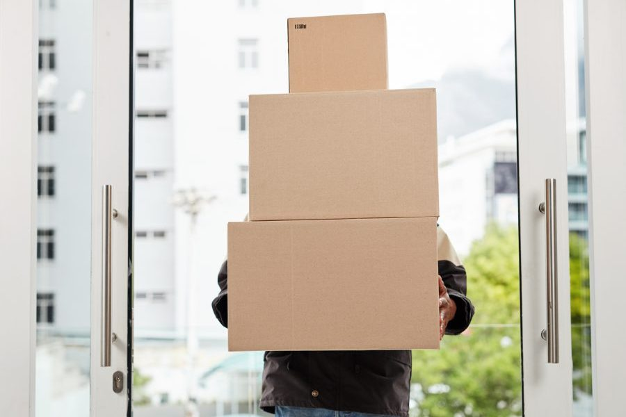 A courier with arms full of packages goes through front door of modern office.