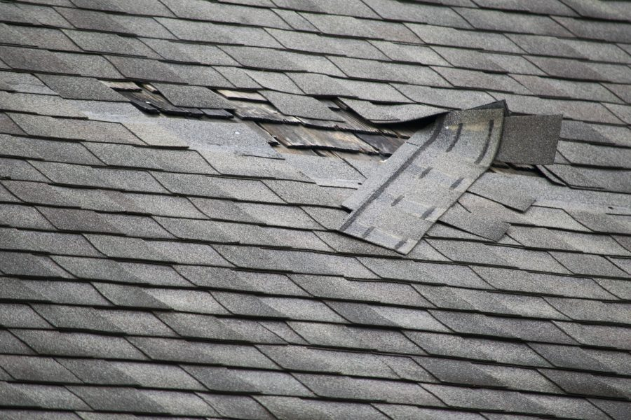 Area of damaged shingles on a roof, surrounded by good shingles.