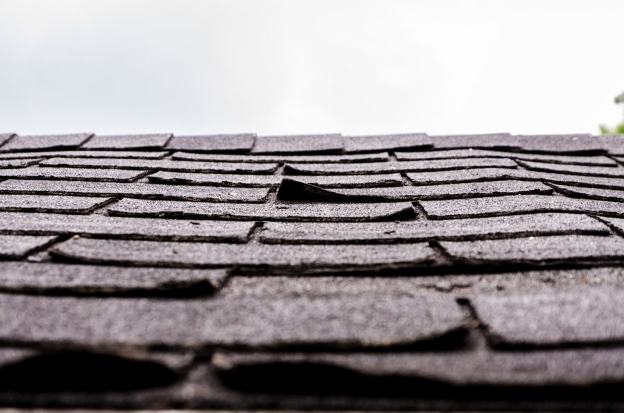 Closeup of curling, worn shingles which could lead to a roof insurance claim.