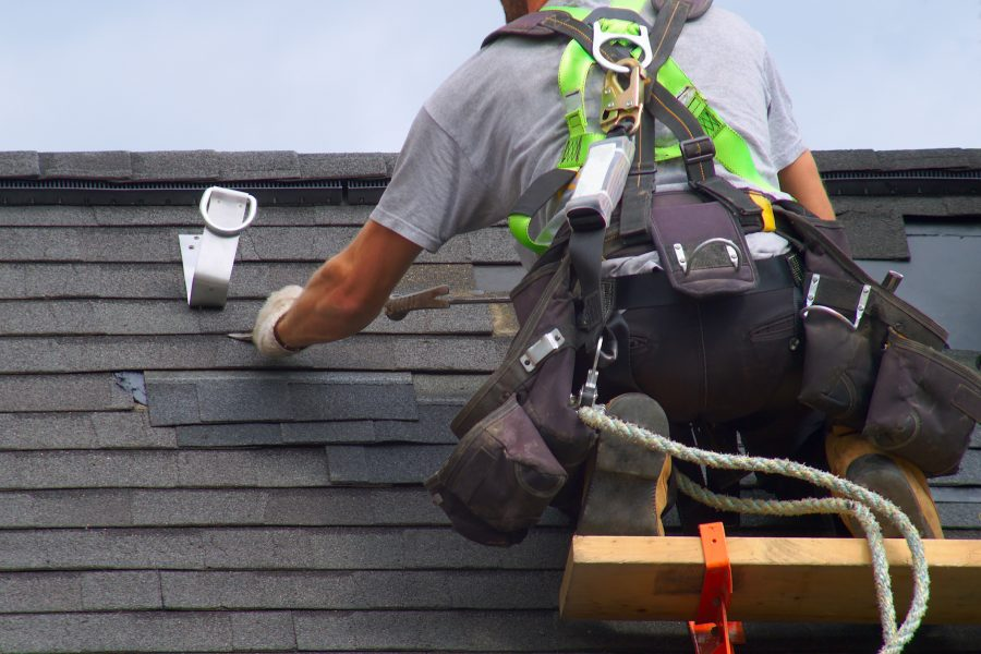 Construction worker repairing a partially damaged roof to avoid a roof insurance claim.