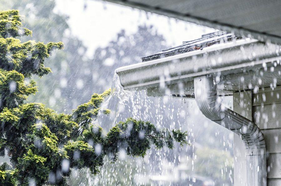 Torrential downpour overflowing from gutter and potentially causing a roof insurance claim.