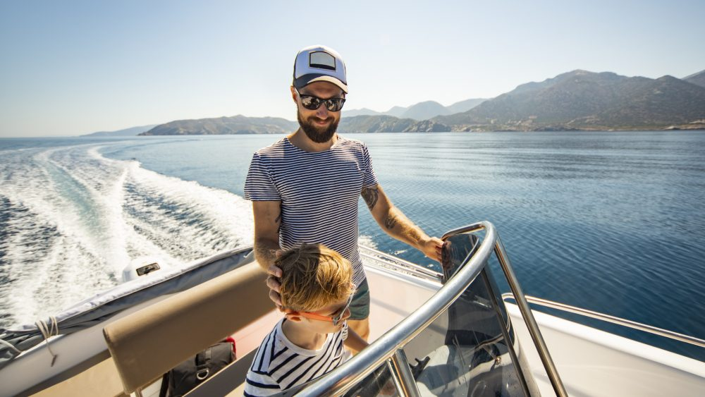 Father and son on boat on lake in mountains.