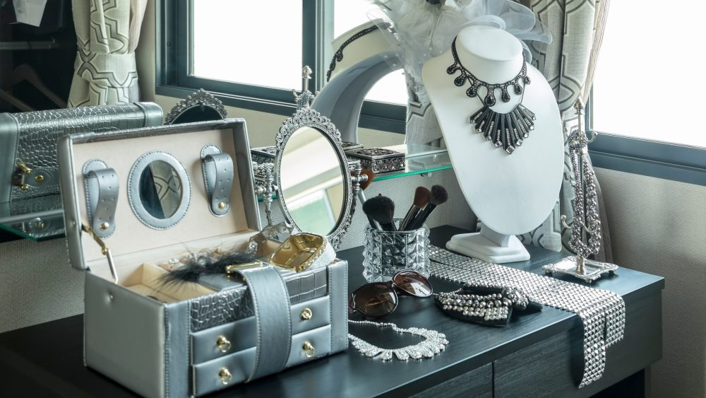 Jewelry box with jewelry on table in front of mirror.