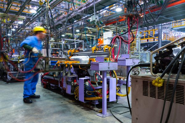 Manufacturing factory floor with employee operating welder illustrating need for equipment breakdown coverage.
