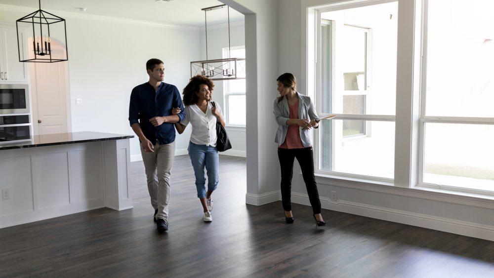 Realtor walks through a vacant home with couple.