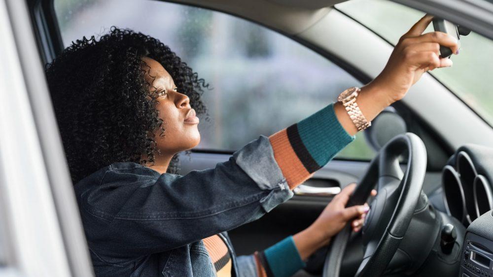 Woman adjusting rearview mirror.